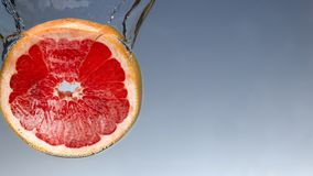 Fresh grapefruit with water splash on blue background close up. Fresh grapefruit with water splash on blue background stock images