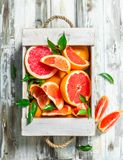 Fresh grapefruit in wooden box. On white wooden background royalty free stock photography