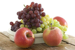 Fresh grapes and apple in a bowl Stock Image
