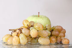 Fresh grapes and apple in water. Healthy food Royalty Free Stock Image