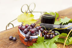 Fresh grapes and bottles of wine Royalty Free Stock Photos
