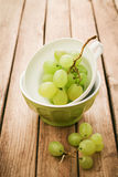 Fresh grapes in cup over wooden background. Food background with retro filter effect Royalty Free Stock Photography