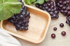 Fresh grapes with leaves in wooden bowl on table. Fresh grapes with leaves in wooden bowl on table background Royalty Free Stock Images