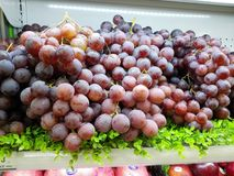Fresh grapes are placed at the supermarket counter for sale Stock Images