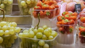 Fresh grapes and strawberries and tropical fruits on the market rack. Fresh grapes and strawberries and tropical fruits on market rack stock footage