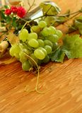 Fresh grapes, vine and vine bottle on wooden Stock Photography