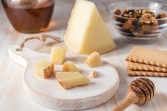 Fresh Greek cheese graviera and a slice on white wooden board royalty free stock photo