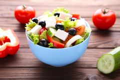 Fresh greek salad on bowl with vegetables on grey wooden background royalty free stock image