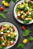 Fresh Greek salad with cucumber, cherry tomato, lettuce, red onion, feta cheese and black olives. Healthy food stock images