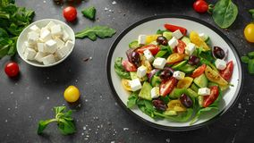 Fresh Greek salad with cucumber, cherry tomato, lettuce, red onion, feta cheese and black olives. Healthy food.  stock photos