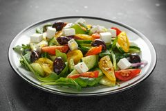 Fresh Greek salad with cucumber, cherry tomato, lettuce, red onion, feta cheese and black olives. Healthy food.  royalty free stock photos