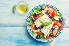 Fresh Greek salad. Of cucumber, tomato, sweet pepper, red onion, feta cheese and olives with olive oil. Healthy food, top view royalty free stock image