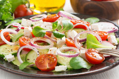 Fresh greek salad with feta cheese on a plate, vertical Stock Image