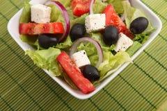 Fresh Greek salad on green background Stock Image