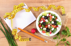 Fresh greek salad with vegetables, centimeter and notepad for writing notes, healthy nutrition and slimming concept. Fresh greek salad with vegetables, tape Stock Images