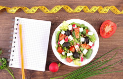 Fresh greek salad with vegetables, centimeter and notepad for writing notes, healthy nutrition and slimming concept. Fresh greek salad with vegetables, tape Royalty Free Stock Photos