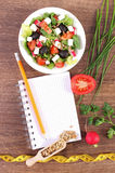 Fresh greek salad with vegetables, centimeter and notepad for writing notes, healthy nutrition and slimming concept. Fresh greek salad with vegetables, tape Royalty Free Stock Photo
