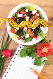 Fresh greek salad with vegetables, centimeter and notepad for writing notes, healthy nutrition and slimming concept. Fresh greek salad with vegetables, tape Royalty Free Stock Images