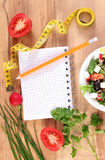 Fresh greek salad with vegetables, centimeter and notepad for writing notes, healthy nutrition and slimming concept. Fresh greek salad with vegetables, tape Stock Image