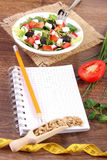 Fresh greek salad with vegetables, centimeter and notepad for writing notes, healthy nutrition and slimming concept. Fresh greek salad with vegetables, tape Stock Photos