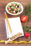 Fresh greek salad with vegetables, centimeter and notepad for writing notes, healthy nutrition and slimming concept. Fresh greek salad with vegetables, tape Royalty Free Stock Photography