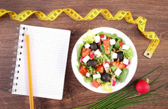 Fresh greek salad with vegetables, centimeter and notepad for writing notes, healthy nutrition and slimming concept. Fresh greek salad with vegetables, tape Royalty Free Stock Image