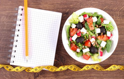 Fresh greek salad with vegetables, centimeter and notepad for writing notes, healthy nutrition and slimming concept. Fresh greek salad with vegetables, tape Stock Photo