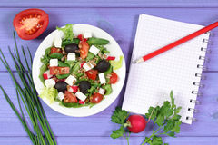 Fresh greek salad with vegetables and notepad for notes, healthy food. Fresh greek salad with vegetables and notepad for writing notes, concept of healthy Stock Images