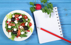 Fresh greek salad with vegetables and notepad for notes, healthy food. Fresh greek salad with vegetables and notepad for writing notes, concept of healthy Royalty Free Stock Photography