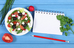 Fresh greek salad with vegetables and notepad for notes, healthy food. Fresh greek salad with vegetables and notepad for writing notes, concept of healthy Royalty Free Stock Photos