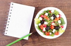 Fresh greek salad with vegetables and notepad for notes, healthy nutrition concept. Fresh greek salad with vegetables and notepad for notes, concept of healthy Stock Photos