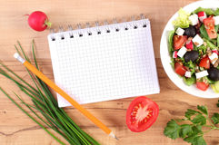 Fresh greek salad with vegetables and notepad for notes, healthy nutrition concept. Fresh greek salad with vegetables and notepad for writing notes, concept of Royalty Free Stock Photography