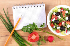 Fresh greek salad with vegetables and notepad for writing notes, healthy nutrition. Fresh greek salad with vegetables and notepad for writing notes, concept of Royalty Free Stock Photos