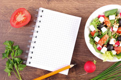 Fresh greek salad with vegetables and notepad for writing notes, healthy nutrition. Fresh greek salad with vegetables and notepad for writing notes, concept of Stock Images