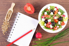 Fresh greek salad with vegetables and notepad for writing notes, healthy nutrition. Fresh greek salad with vegetables and notepad for writing notes, concept of Stock Photography