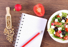 Fresh greek salad with vegetables and notepad for writing notes, healthy nutrition Stock Photos