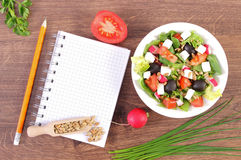 Fresh greek salad with vegetables and notepad for writing notes, healthy nutrition. Fresh greek salad with vegetables and notepad for writing notes, concept of Stock Photo