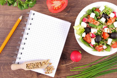 Fresh greek salad with vegetables and notepad for writing notes, healthy nutrition. Fresh greek salad with vegetables and notepad for writing notes, concept of Royalty Free Stock Photo