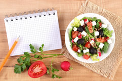 Fresh greek salad with vegetables and notepad for writing notes, healthy nutrition. Fresh greek salad with vegetables and notepad for writing notes, concept of Royalty Free Stock Images