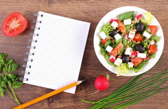 Fresh greek salad with vegetables and notepad for writing notes, healthy nutrition. Fresh greek salad with vegetables and notepad for writing notes, concept of Stock Image