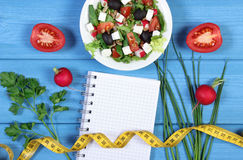 Fresh greek salad with vegetables, tape measure and notepad for notes, healthy food and slimming concept. Fresh prepared greek salad with vegetables, tape Royalty Free Stock Photos