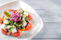 Fresh Greek salad on white plate with onion. Close up with selective focus Royalty Free Stock Images