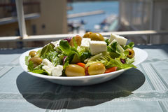 Fresh Greek salad on a white plate in the sun Stock Photo