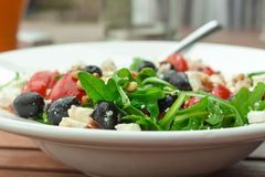 Fresh greek style salad with ruccola, tomatoes, pine kernels. Stock Photo