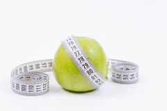 Fresh green apple diet. Measurement tape around fresh green apple.Image concept for healty life and diet Stock Photography