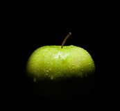 Fresh green apple with droplets of water against black background Royalty Free Stock Images