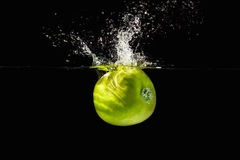 Fresh green apple falling in water with splash Royalty Free Stock Photo