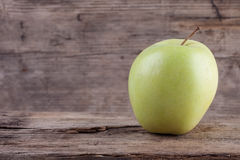 Fresh green apple on grunge old wooden background Stock Images