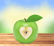 Fresh green apple with heart on wooden table over nature Stock Photography