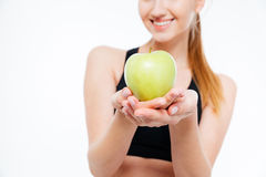 Fresh green apple holded by cheerful woman athlete Royalty Free Stock Photos